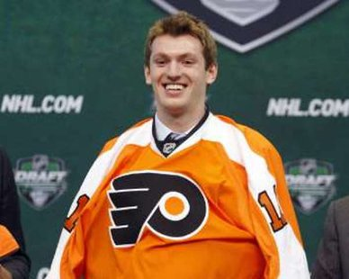 Sean Couturier puts on a Philadelphia Flyers jersey after being picked in the first round at the 2011 NHL hockey draft in St. Paul, Minnesota, June 24, 2011. REUTERS/Eric Miller