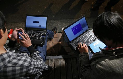 Men install Microsoft Corp's Windows 8 operating system on their laptops, as Windows 8 goes on sale after midnight, along a street at the Ak