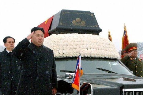 North Korea's new leader Kim Jong-un (2nd L) salutes as he and his uncle Jang Song-thaek (L) accompany the hearse carrying the coffin of lat