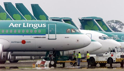 Ground crew are seen parking an Aer Lingus Airbus A320 away from the passenger terminals at Dublin Airport, in the Republic of Ireland in th