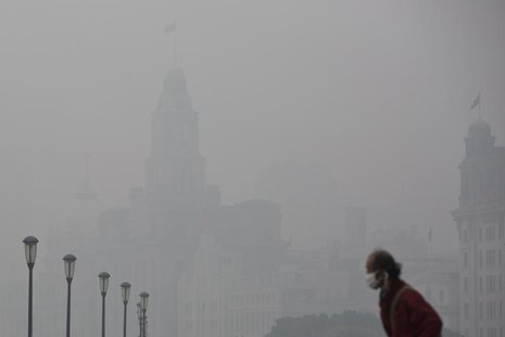 A man wears a face mask while walking on the Bund during a hazy day in downtown Shanghai December 6, 2013. REUTERS/Aly Song