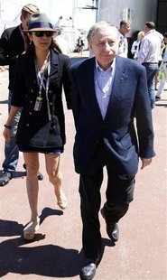 Former Ferrari team manager and FIA President Jean Todt and his girlfriend Michelle Yeoh walk in the paddock area before the Monaco F1 Grand