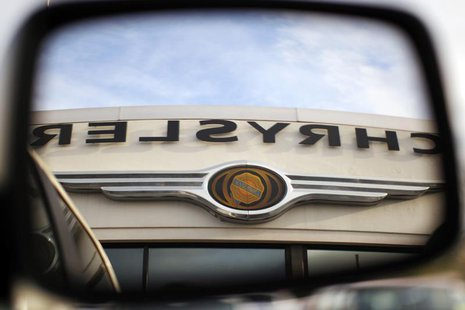 The Chrysler logo is reflected in the rear view mirror of a vehicle on the lot at Clark Chrysler Jeep Dodge dealership in Methuen, Massachus