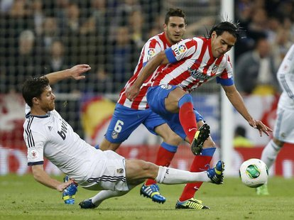 Real Madrid's Xabi Alonso (L) challenges Atletico Madrid's Radamel Falcao during their Spanish King's Cup final soccer match at Santiago Ber