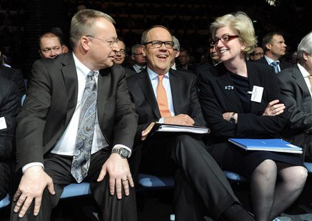 Nokia's Chief Executive Stephen Elop (L), Chairman of the Board Jorma Ollila (C), and Vice Chairman Dame Marjorie Scardino (R) take part in