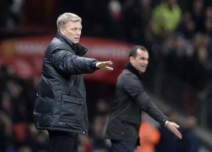 Manchester United manager David Moyes (L) and Everton manager Roberto Martinez direct their teams during their English Premier League soccer