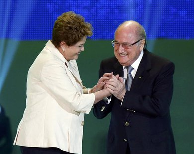 Brazilian President Dilma Rousseff (L) and FIFA President Sepp Blatter react on stage during the draw for the 2014 World Cup at the Costa do