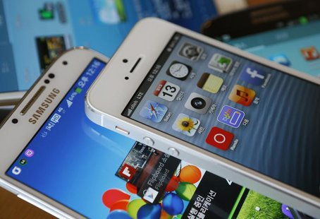 Apple's iPhone 5 (top) and Samsung Electronics' Galaxy S4 are seen in this picture illustration taken in Seoul May 13, 2013. REUTERS/Kim Hon