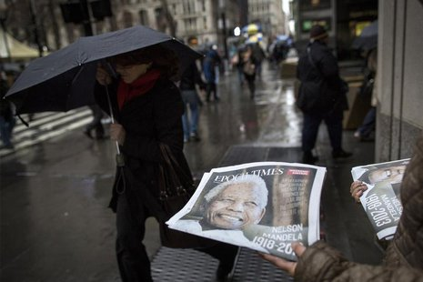A woman distributes a newspaper featuring the late Nelson Mandela on the front page in New York, December 6, 2013. REUTERS/Brendan McDermid