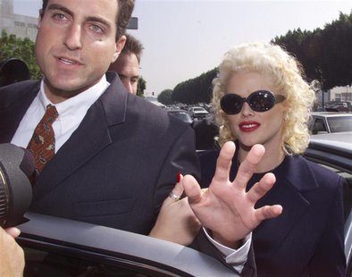 Model and former Playboy magazine Playmate Anna Nicole Smith is escorted by an unidentified attorney from her car as she arrives for opening
