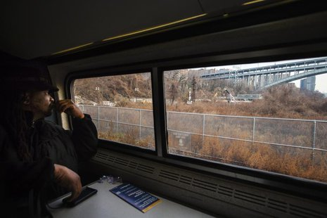 Passenger James Earl looks out of the window of an Amtrak train as it passes the site of a derailed Metro-North Railroad train in New York,