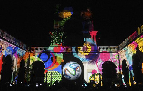 "People take pictures of the official match ball for the 2014 World Cup named ""brazuca"" which is projected on a building at Lage Park during"