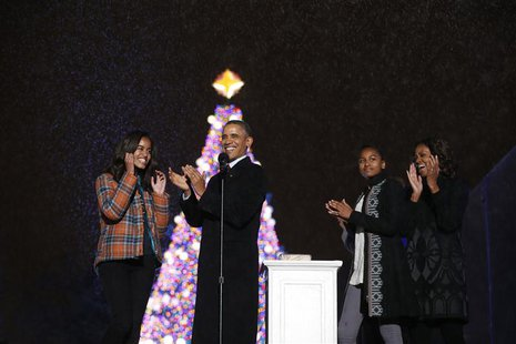 U.S. President Barack Obama applauds as he is joined by daughters Malia (L) and Sasha and First Lady Michelle Obama, after lighting the Nati
