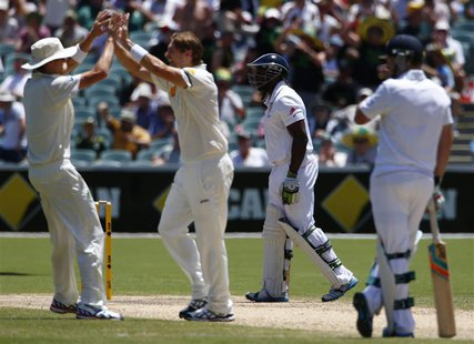 England's Michael Carberry (2nd R) walks off the field after his dismissal, as Australia's Shane Watson (2nd L) and Ryan Harris (L) celebrat