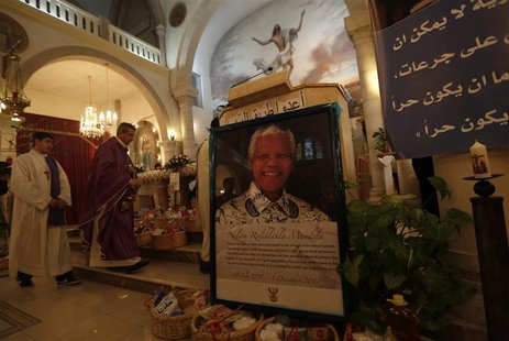 A poster depicting former South African President Nelson Mandela is displayed during a special service in his honour at the Holy Family Chur