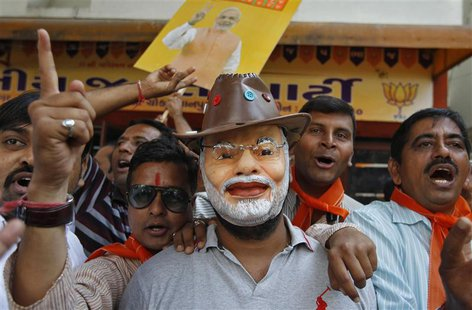A supporter wearing a mask of Gujarat's chief minister and Hindu nationalist Narendra Modi, the prime ministerial candidate for India's main