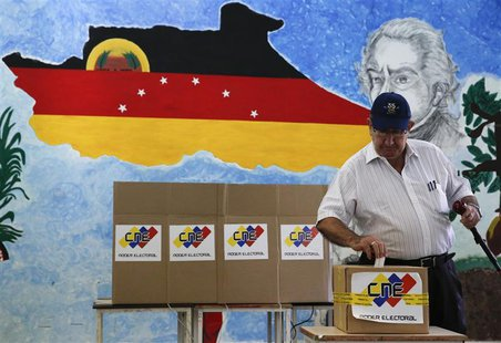 A man casts his ballot in a box during a municipal elections in Caracas December 8, 2013. REUTERS/Carlos Garcia Rawlins