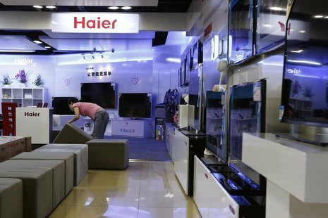 An employee arranges stools at a section displaying Haier television sets inside a Suning store in Shanghai August 26, 2013. REUTERS/Aly Son