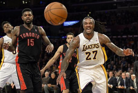 Dec 8, 2013; Los Angeles, CA, USA; Los Angeles Lakers center Jordan Hill (27) and Toronto Raptors power forward Amir Johnson (15) watch as t