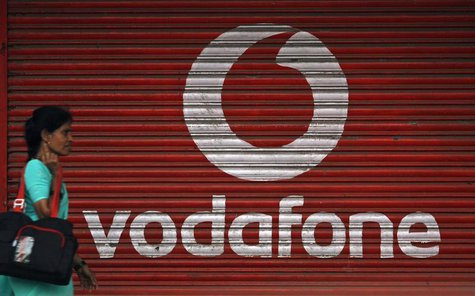 A woman walks past a large logo of Vodafone displayed on a shop in Mumbai May 20, 2010. REUTERS/Arko Datta
