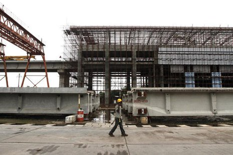 A man walks past a light rail station under construction at the Orile-Iganmu district in Lagos August 29, 2013. REUTERS/Akintunde Akinleye