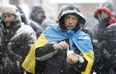 A protester holds a piece of bread as he gathers with others at Independence Square during a rally to support EU integration in Kiev Decembe