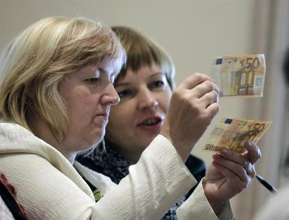 People learn to differentiate between original (bottom) and counterfeit euro banknotes during a workshop in Salacgriva September 24, 2013. R
