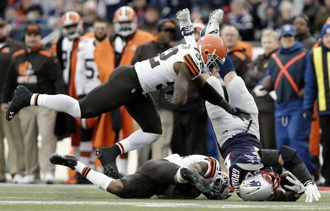 Dec 8, 2013; Foxborough, MA, USA; New England Patriots tight end Rob Gronkowski (87) is tackled by Cleveland Browns strong safety T.J. Ward