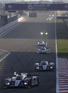 Race cars compete during the start of the final race of the 2013 World Endurance Championship (WEC) Six Hours of Bahrain at the Bahrain Inte