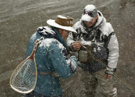 Fly fishermen Mike Gasiecki (R) and guide Dan Soper re-tie their lures on the north fork of the south branch of the Potomac River during a winter blizzard in Hopeville Canyon, West Virginia December More... CREDIT: REUTERS/GARY CAMERON