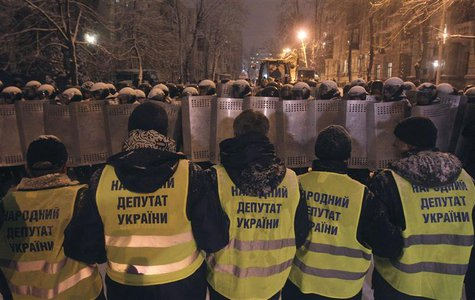 REFILE - ADDING ADDITIONAL INFORMATION Supporters of EU integration line up in front of riot police with shields during a rally in Kiev, Dec