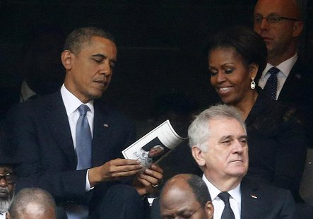 U.S. President Barack Obama (back L) and his wife, first lady Michelle Obama look at the official program booklet during the memorial servic