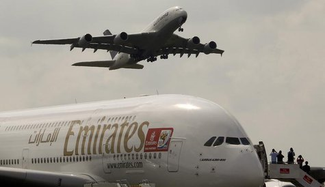 An Airbus A380 aircraft of Deutsche Lufthansa (top) takes of passing over an Airbus A380 aircraft of Emirates at the ILA International Air S