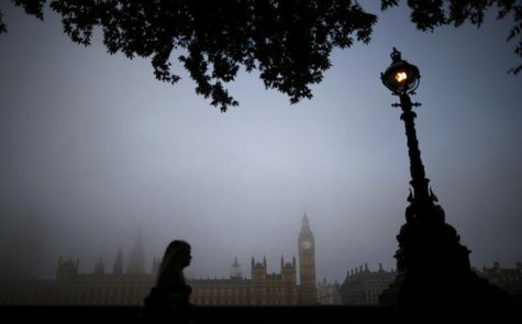 A woman walks along the south bank of the Thames opposite the Houses of Parliament on a foggy morning in London September 24, 2013. REUTERS/
