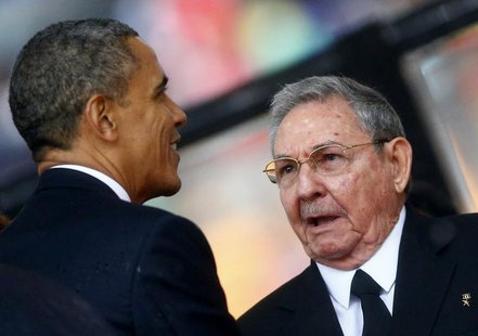 U.S. President Barack Obama (L) greets Cuban President Raul Castro before giving his speech at the memorial service for late South African P