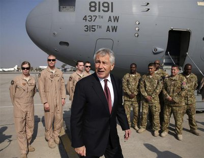 U.S. Secretary of Defense Chuck Hagel stands with U.S. troops before departing from Islamabad International Airport December 9, 2013. REUTER
