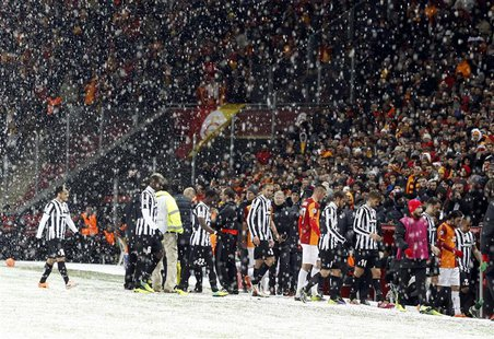 Players of Galatasaray and Juventus walk out of the pitch as their match is paused for 20 minutes due a heavy snowfall during their Champion