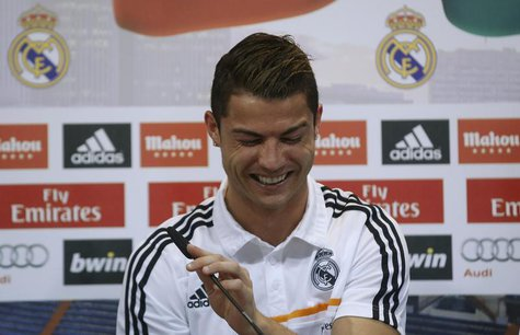 Real Madrid's Cristiano Ronaldo reacts as he attends a news conference to discuss the draw for the 2014 World Cup at the Valdebebas training