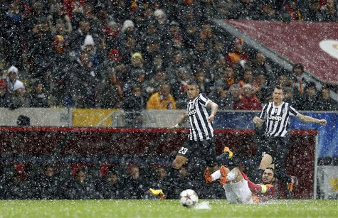 Arturo Vidal of Juventus (L) runs for the ball past Selcuk Inan of Galatasaray (bottom) during their Champions League soccer match in Istanb