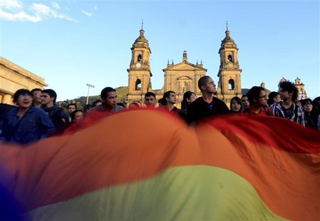 Supporters of Bogota's mayor Gustavo Petro wave an LGBT flag during a protest against his removal at Bogota's Bolivar Square December 10, 20