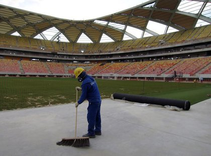 A workman next to the pitch inside the Arena Amazonia stadium as work continues in preparation for the 2014 FIFA World Cup soccer championsh