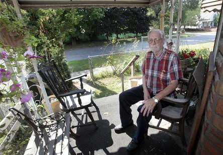 Les Cadman sits on the front porch of his home located across the street from where the plaza for a new international bridge is slated to be