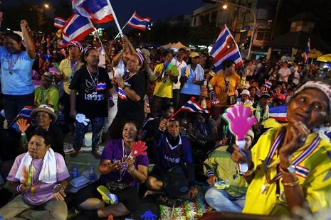 Anti-government protesters dance as they wait for their leader Suthep Thaugsuban to address them from the stage near the Government house in