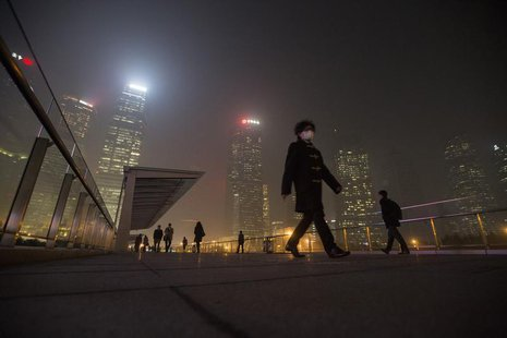 A man wears a mask while walking on a bridge during a hazy night in Shanghai's financial district of Pudong December 5, 2013. REUTERS/Aly So