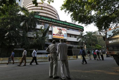 People watch a large screen displaying India's benchmark share index on the facade of the Bombay Stock Exchange (BSE) building in Mumbai Dec