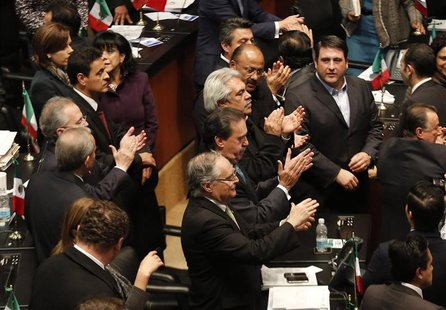Senators of the ruling Institutional Revolutionary Party (PRI) applaud after Mexico's Senate signed off on an energy bill at the Senate buil