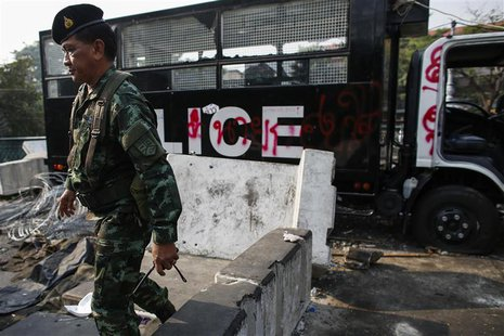 A soldier walk past a destroyed police truck near Government House, where anti-government protesters are gathered, in Bangkok December 11, 2