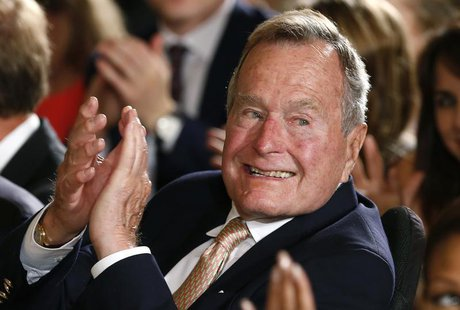 Former President George H. W. Bush applauds during an event to honor the winner of the 5,000th Daily Point of Light Award at the White House