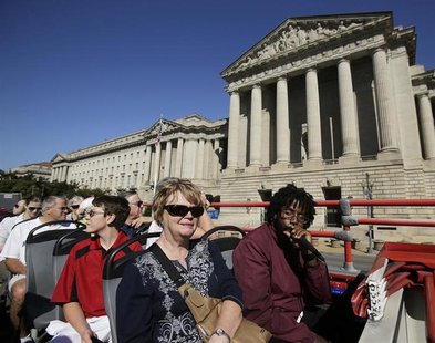 Tourists, with guide Darnell Lacy (R), pass by the closed National Archives building in Washington atop a Big Bus double-decker tour bus. RE