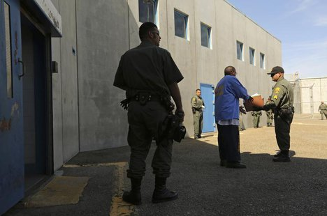 An inmate (C) is checked by guards after leaving a general population cell block, in Corcoran State Prison, California October 1, 2013. REUT